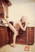 Beautiful athletic leg split flexible smiling young blond woman pinup girl sweeping the floor in the kitchen & looking at camera — Stock Photo