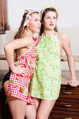 Girl friends standing in aprons — Stock Photo