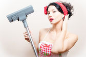 Closeup portrait on funny charming young beautiful brunette woman pin-up girl with vacuum cleaner raised in hand straightens her hair — Stock Photo