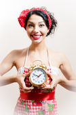 Young beautiful funny pinup young woman attractive girl with big smile holding alarm clock looking at camera background — Stok fotoğraf