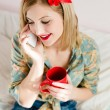 Girl  holding cup and talking on mobile cell phone — Stock Photo #42592033