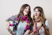 Girl friends having fun wearing knitted scarf — Stock Photo
