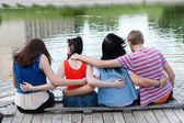 Teenage friends sitting on bridge at the river — Stock Photo