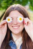 Girl  holding flowers on eyes — Stock Photo