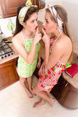 Young beautiful funny women pinup girls at the kitchen in aprons showing silence sign — Stock Photo