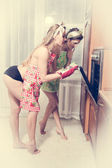 Two seductive young pinup women beautiful girls at the kitchen near oven — Zdjęcie stockowe