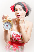 Agitated funny young brunette blue eyes pinup woman with alarm-clock looking at camera — Stock Photo