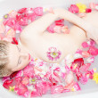 Woman  lying in the bath with rose petals — Stock Photo #43496629