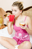 Woman  on bed drinking beverage from red cup — Stock Photo