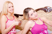 Women sitting in bed  one doing other braid pigtail — Stock Photo