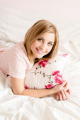 Woman in bed with floral pillow — Stock Photo