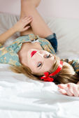 Woman with red ribbon on head  lying on bed — Foto Stock
