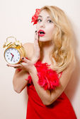Woman in red dress holding alarm-clock — Stock Photo