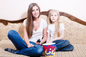 Young woman with girl  watching movie, eating popcorn — Stock Photo