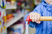Childs hand holding shopping cart — Stock Photo