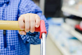 Little child hand holding shopping trolley — Stock Photo