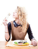 Woman eating sushi with chopsticks — Stock Photo