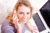 Woman  talking on the smart phone, working on laptop — Stock Photo