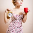 Woman holding golden alarm-clock & cup of drink — Stock Photo #44772669