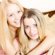 Women in pajamas hugging on white bed — Stock Photo