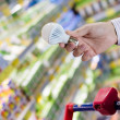 Choosing energy efficient lighting: closeup on male or female hand holding or selecting LED diode light bulb lamp in DIY department store with product display shelfs shop on the background — Zdjęcie stockowe