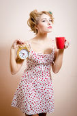 Woman holding golden alarm-clock & cup of drink — Stock Photo