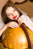 Student smiling  at the globe — Stock Photo
