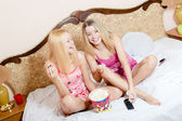 Womenin bed with popcorn, watching TV — Stock Photo