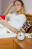 Woman in bed with red cup and alarm clock — Foto de Stock