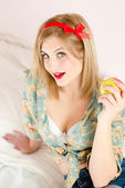 Beautiful blond young woman blue eyes sexy pinup girl holding apple & looking at camera sitting in white bed — Stock Photo