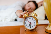 Man pulling his hand  to the alarm clock — Stock Photo