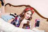 Jeune fille se détendre au lit pointant sur téléphone mobile — Photo