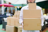 Young man holding, carrying or moving three boxes in the store background — Stock Photo