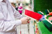 Closeup su uomo d'affari selezionando o scegliendo e acquistando una scopa spazza per pavimento o percorso il reparto fai da te shopping negozio sfondo — Foto Stock