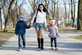 Mom walking with her son and daughter — Stock Photo