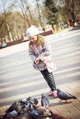 Beautiful little girl feeding pigeons — Stock Photo