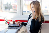 Woman talking on the phone working on a laptop — Stock Photo