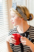 Woman with a red cup looking  out the window — Stock Photo