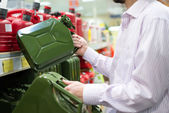 Man holding two size green cans in a supermarket — Foto Stock
