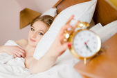 Blonde touching alarm wake up — Stock Photo