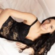 Closeup portrait of beautiful sensual brunette young woman with blue eyes having fun relaxing lying in black lingerie on white bed happy smiling and looking into the camera picture — Stock Photo #49366513