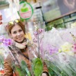 Nice woman holding an orchid in hands smiling looking at the camera in a supermarket — Stock Photo #49368747
