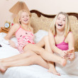 Joyful foot massage treatment: beautiful blond girl friends having fun relaxing while younger sister making foot massage older sister on a white bed happy laughing looking at camera — Stock Photo