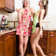 Two seductive beautiful brunette & blond young women in apron laughing in kitchen having fun relaxing portrait image — Stock Photo #49369847