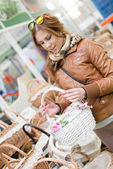 Charming woman holding a basket in her hands looking smiling in supermarket — Stock Photo