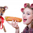 While adorable cute dog looking at camera pinup beautiful funny blond young woman with blue eyes & curlers having fun eating a hot dog & happy smiling on a white background closeup portrait image — Stock Photo #49371417