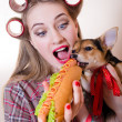 Funny pinup small cute dog & beautiful blond sexy young woman with curlers looking surprised having fun eating a hot-dog on a white background closeup portrait image — Stock Photo #49371519