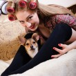 Closeup portrait cute small dog & beautiful blond young pinup woman with blue eyes having fun relaxing lying in bed looking into the camera and happy smiling image — Stock Photo #49371591