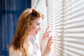 Beautiful young pinup woman looking through white window blinds — Stock Photo