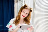 Beautiful young pinup woman reading on tablet pc and smiling at home by window blinds — Foto de Stock